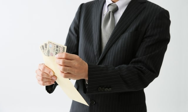 封筒の金を持つスーツ